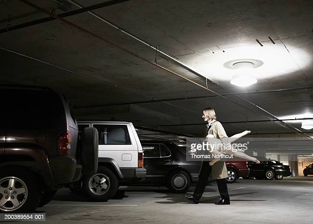 Young businessman carrying blow-up doll in parking garage, side view