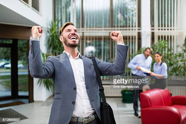 Young businessman celebrating success with arms raised.