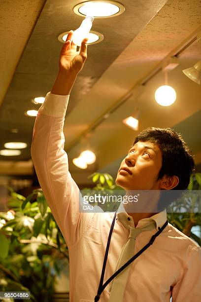 Young Businessman Changing A Lightbulb