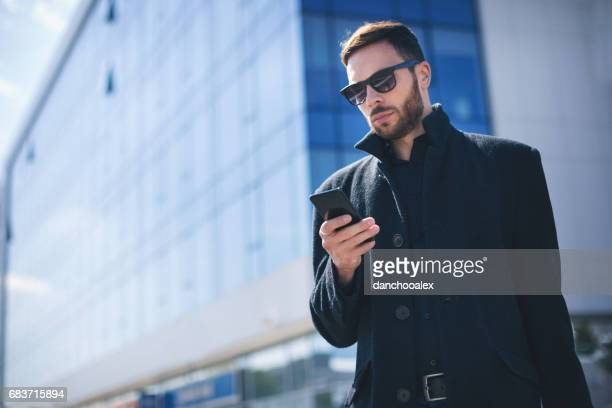 Young businessman checking his smart phone
