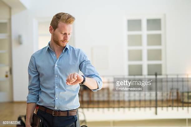 Junger Geschäftsmann überprüfen die Zeit auf seine Armbanduhr.