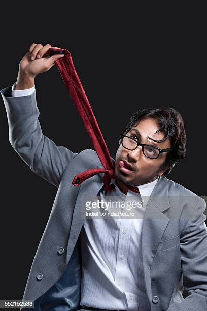 Young businessman committing suicide against black background