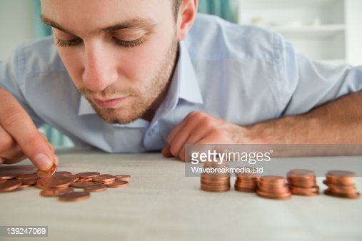 Businessman counting coins : Stock Photo