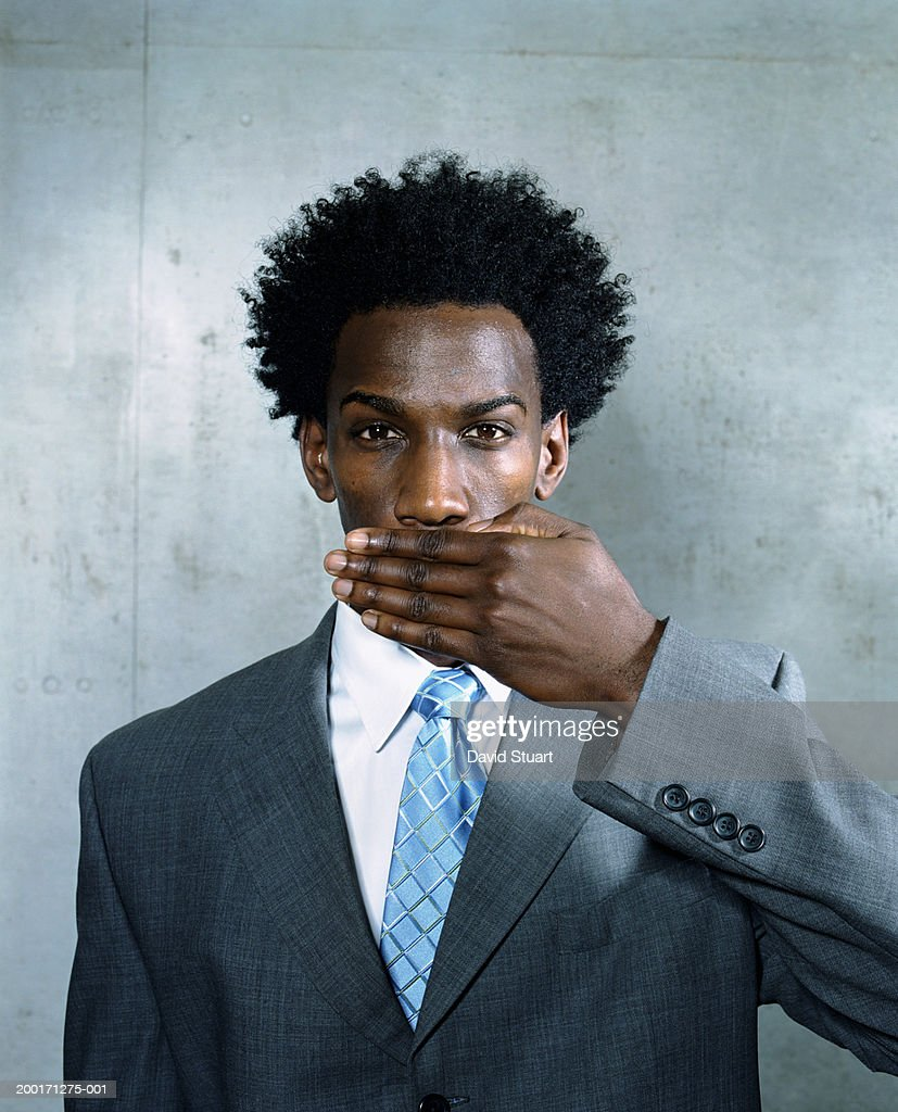 Young businessman covering mouth with hand, portrait