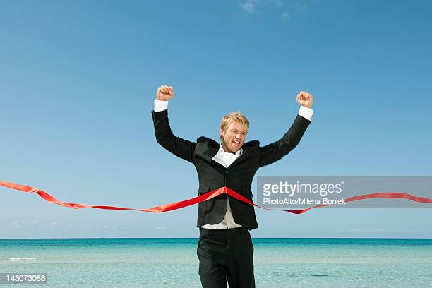 Young businessman crossing finishing line
