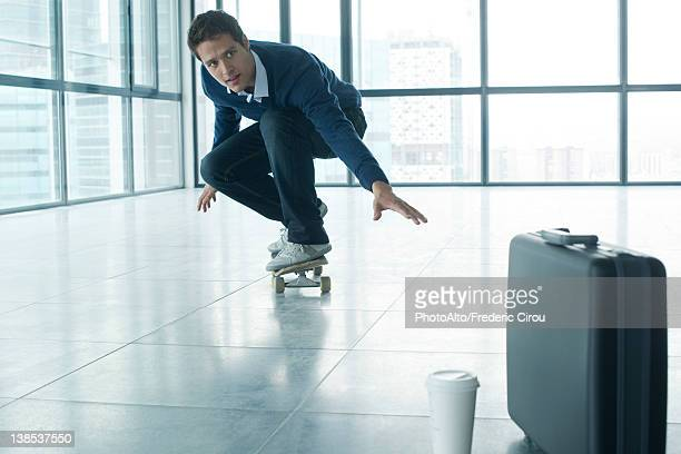 Young businessman crouching on skateboard, coffee cup and briefcase in foreground