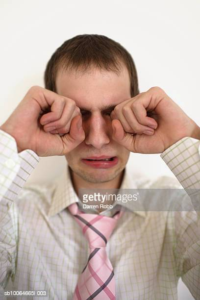 Young businessman crying and rubbing eyes