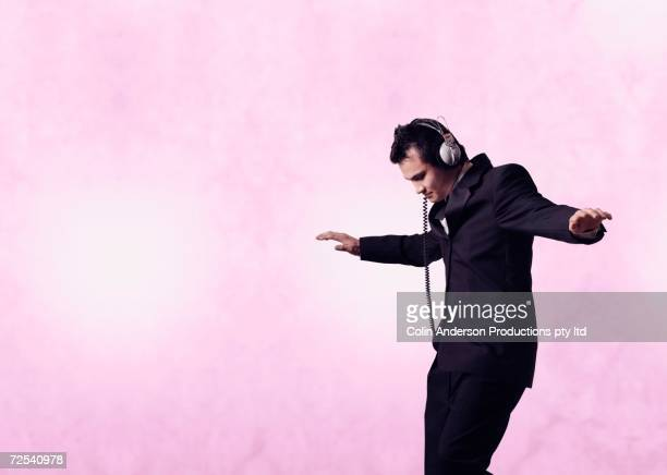 Young businessman dancing and wearing headphones
