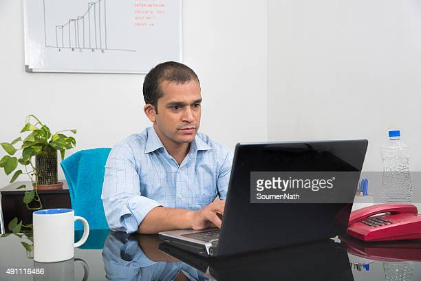 Young Businessman deeply engrossed while working on his Laptop