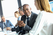 Young businessman discussing with female colleague in meeting room