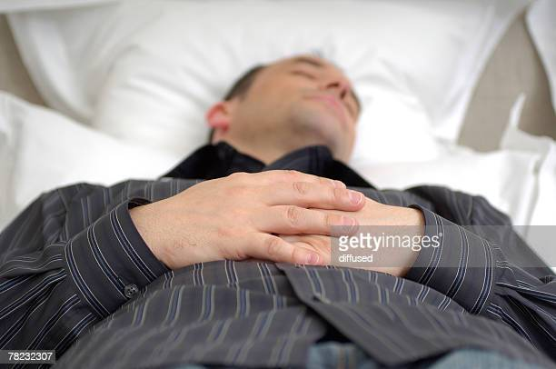 young businessman dozing in bed with folded hands