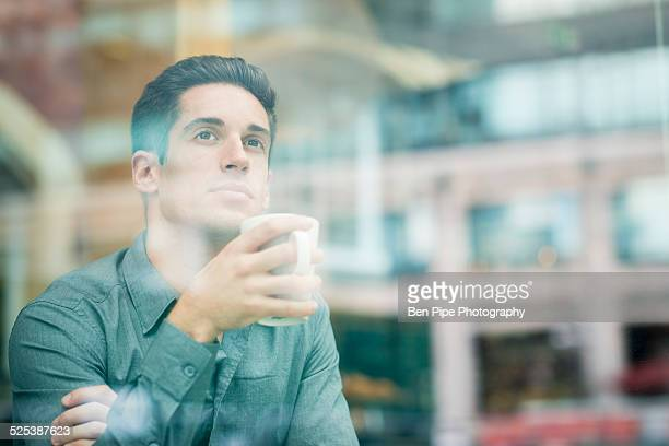 Young businessman drinking coffee and looking out of cafe window, London, UK