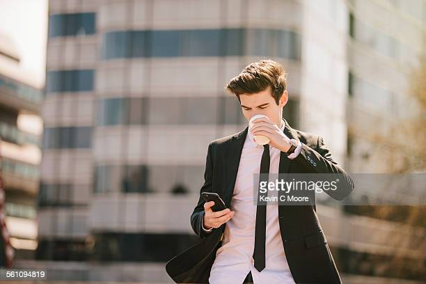 Young businessman drinking take away coffee whilst reading smartphone texts