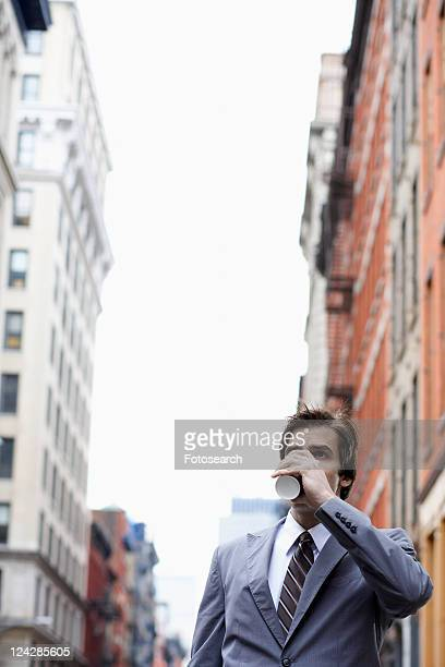 Young businessman drinking takeout coffee on street
