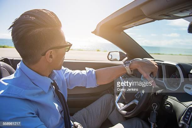 Young businessman driving convertible at coast