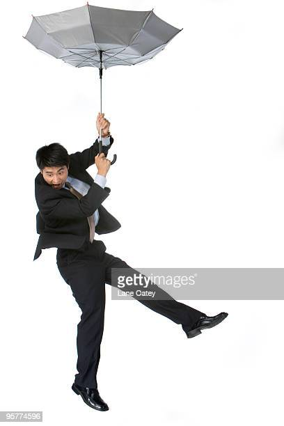 Young businessman dropping down by umbrella