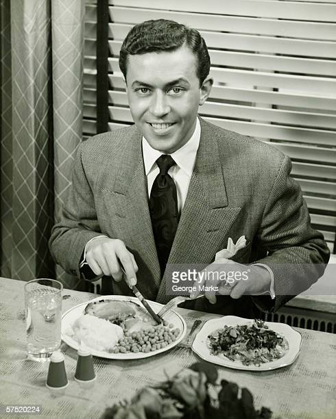Young businessman eating dinner, (B&W), portrait