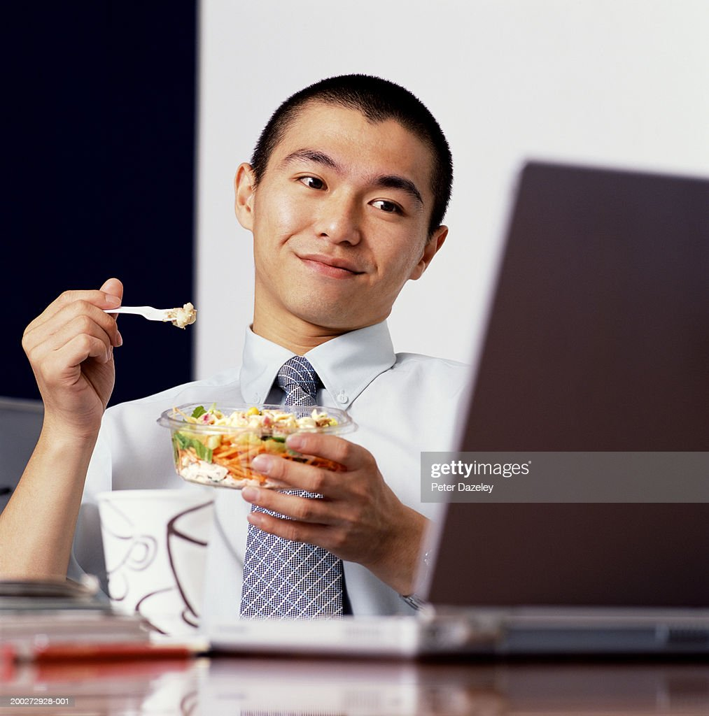 Young businessman eating  lunch at desk, looking at laptop : Stock Photo