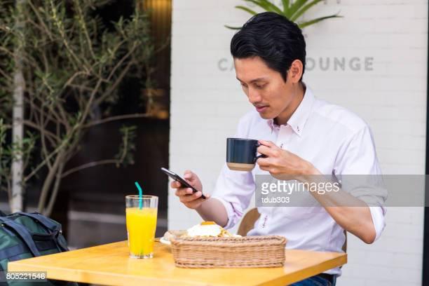 Junger Geschäftsmann, genießen das Frühstück in einem Hotel während der Arbeit
