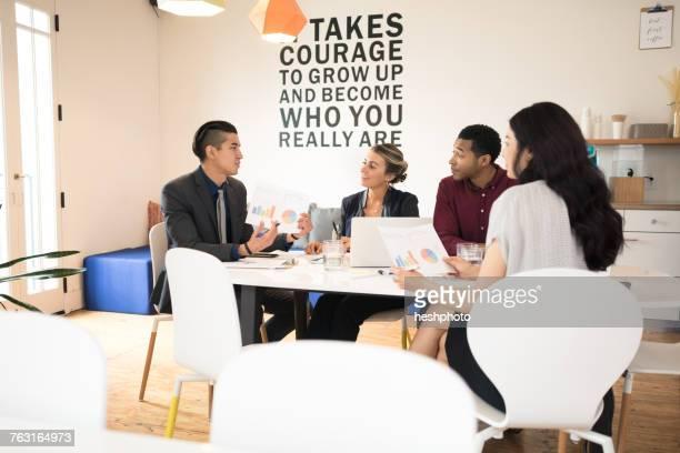 Young businessman explaining at team meeting