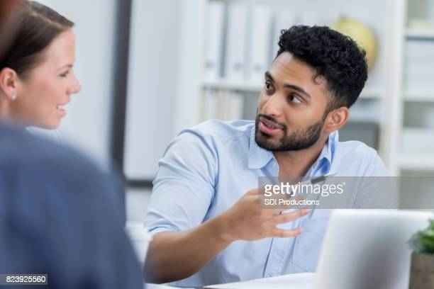 Young businessman explains new idea to coworker