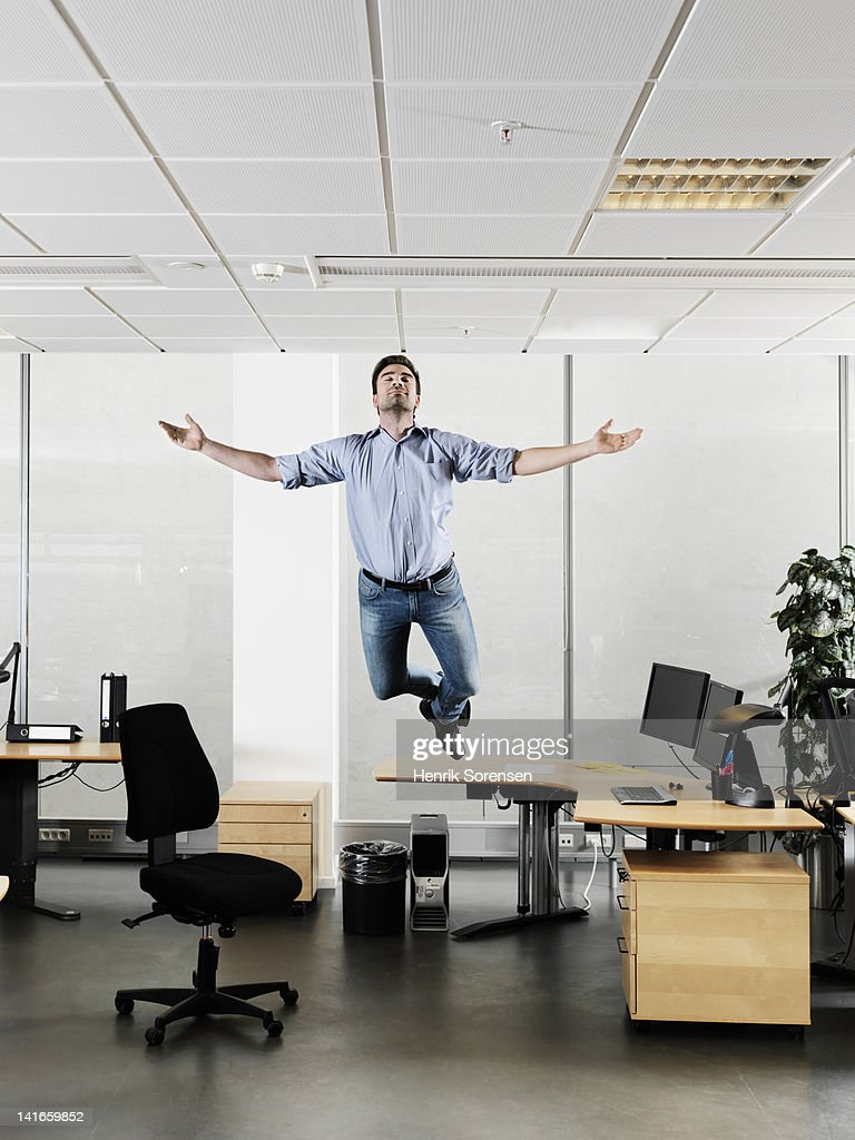 young Businessman floating above the desk