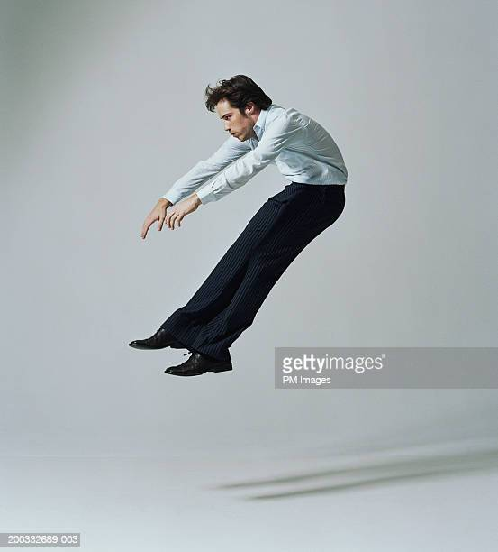 Young businessman flying backwards, side view