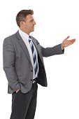 Young businessman looking left, gesturing, talking..