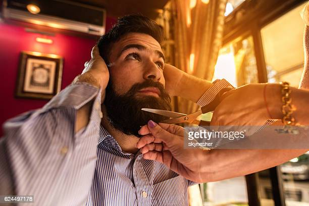 Young businessman getting his beard cutted by unrecognizable person.