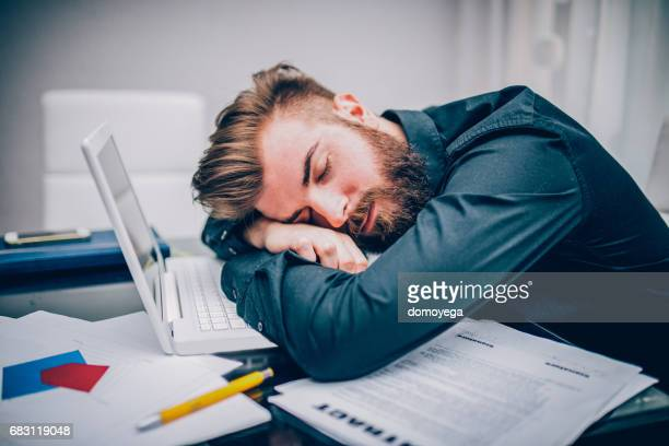 Young businessman getting tired and depressed working hard in the office