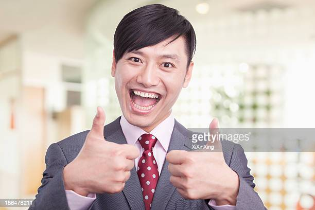 Young businessman giving the thumbs up sign, portrait