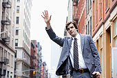 Young businessman hailing taxi cab