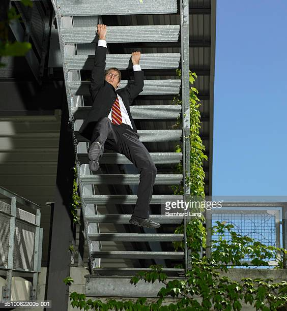 Young businessman hanging on stairs, low angle view