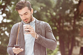 Young businessman having coffee while using smart phone outdoors