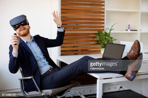 Young businessman having fun with VR simulator
