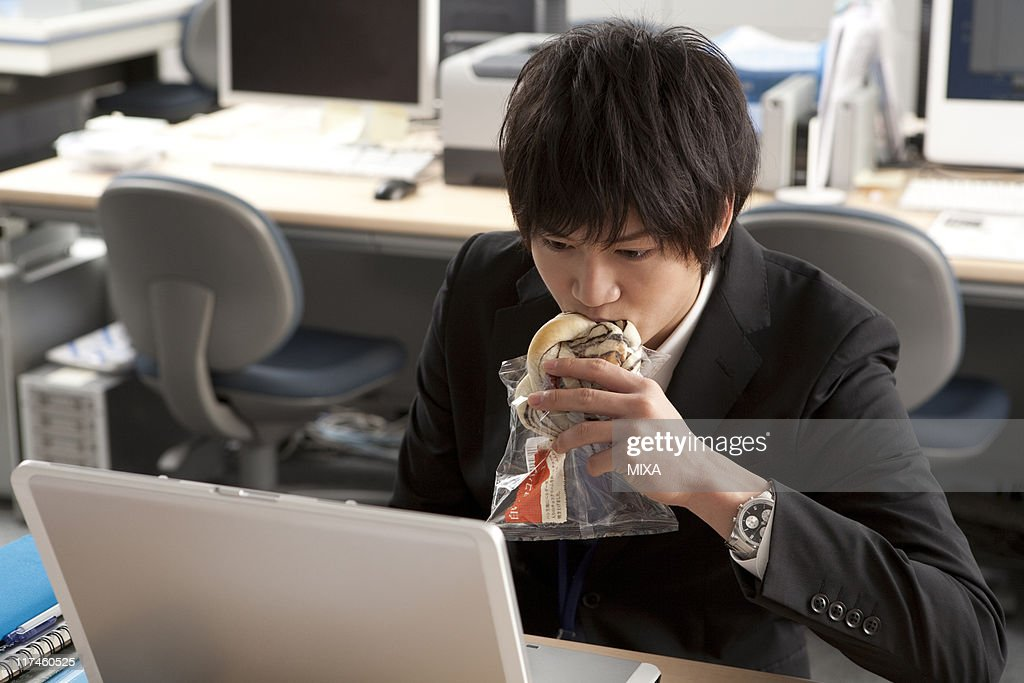 Young businessman having meal at desk : Stock Photo