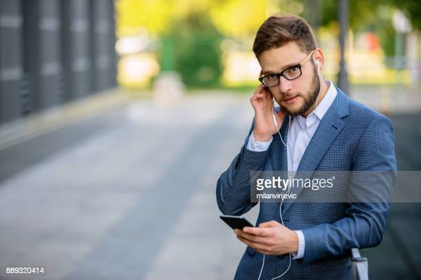 Young businessman having phone call outdoors