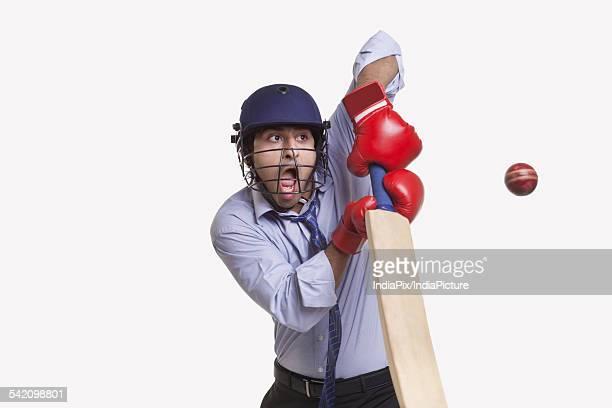 Young businessman hitting ball