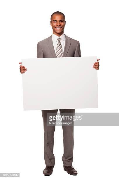 Jeune homme d'affaires tenant un panneau vierge. Isolé.
