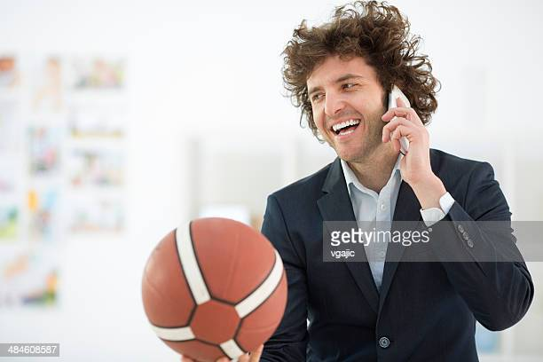 Young Businessman Holding Basketball Ball and talking on the phone.