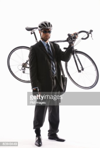 Young businessman holding bicycle over shoulder : Stock Photo