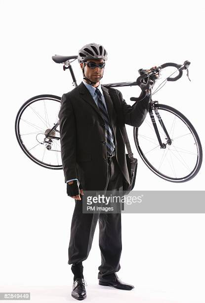 Young businessman holding bicycle over shoulder