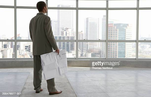 Young businessman holding blueprint in empty building, rear view