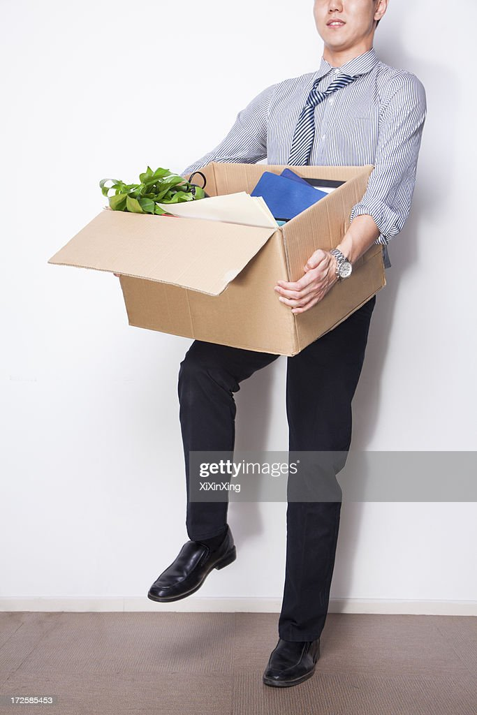 Young Businessman holding box of office items