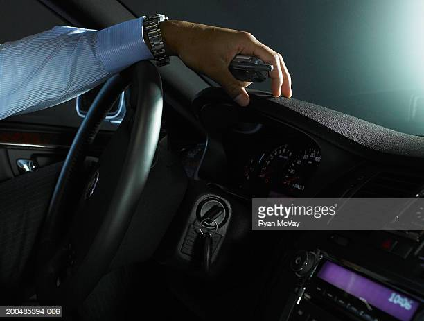 Young businessman holding cell phone in car, close-up of hand