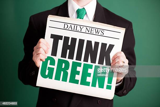 Young Businessman Holding Newspaper Headlined 'Think Green!'