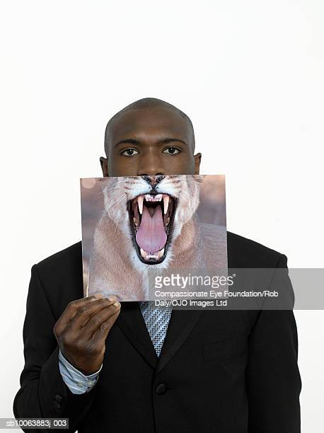 Young businessman holding picture of lion's mouth, portrait