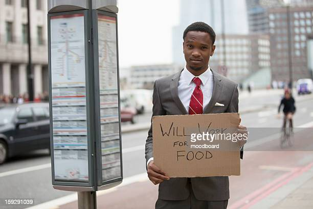 Young businessman holding ''Will Work for Food'' sign at street