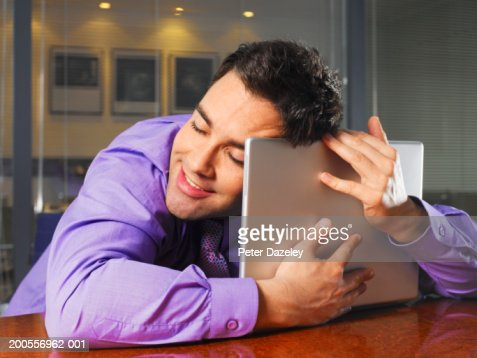 Young businessman hugging laptop, close-up : Stock Photo
