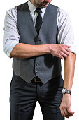 A young businessman in a white shirt rolls up his sleeves preparing to work. A guy, a hipster in a gray waistcoat with a black tie. Ready for work